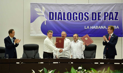 Aspecto de la ceremonia de firma del cese bilateral al fuego. Timoleón Jiménez y Juan Manuel Santos con los acuerdos en la mano. Foto Presidencia.
